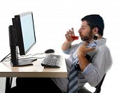 pic of alcohol abuse  - young alcoholic business man drinking whiskey sitting drunk at office with computer holding glass of alcohol looking depressed and in crisis wearing loose tie in addiction problem concept isolated white background - JPG