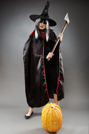 picture of sorcerer  - Full length of a sorcerer with hat and cape over gray background ready to cut a pumpkin with an axe - JPG