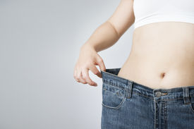 image of slender  - The concept of weight loss. Beautiful slender female body. Young woman in jeans large size. ** Note: Soft Focus at 100%, best at smaller sizes - JPG