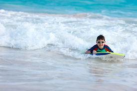 picture of boogie board  - Little boy on vacation having fun swimming on boogie board - JPG