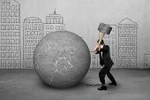 pic of stress-ball  - businessman holding hammer hitting cracked concrete ball with city buildings doodles background - JPG