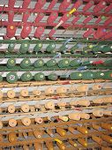 stock photo of loom  - Cylinders with red green and yellow wool threads for a weaving loom in Geelong in Australia - JPG