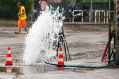 foto of cone  - road spurt water beside traffic cones - JPG
