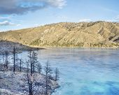 foto of collins  - pine trees bunt by wildfire on the shore of frozen Seaman Reservoir in Rocky Mountains near Fort Collins - JPG