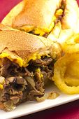 foto of cheesesteak  - A messy Philly Cheesesteak with onions peppers and mushrooms onion rings on the side - JPG