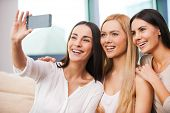 picture of couch  - Three beautiful young women making selfie and smiling while sitting on the couch together - JPG