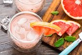 stock photo of cocktail  - Cocktail with grapefruit slice on a wooden table - JPG