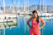 foto of sloop  - Beautiful young girl standing in front of the sailing boats and posing in the harbour - JPG