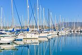 stock photo of sloop  - Panorama of a big Gouvia harbour with white yachts and boats on a beautiful sunny day over the island of Corfu - JPG