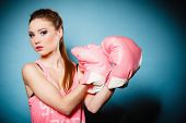 foto of big-girls  - Funny girl female boxer model wearing big fun pink gloves playing sports boxing studio shot blue background - JPG