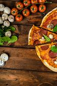 foto of salami  - Rustic pizza with salami mozzarella and spinach on a clay plate - JPG