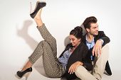 foto of lovers  - Happy fashion couple sitting together on the floor laughing while looking away from the camera - JPG