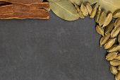 stock photo of cassia  - Cassia bark bay leaves cardamom on a gray background - JPG
