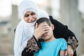stock photo of eastern culture  - Arabic Muslim Middle Eastern woman with olive branch and son crying - JPG