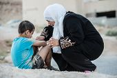 stock photo of eastern culture  - Arabic Muslim Middle Eastern poor woman with her son on dirty ground - JPG