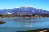 foto of snow capped mountains  - View of Lake Vinuela with snow capped mountains to the rear La Vinuela Costa del Sol Malaga Province Andalusia Spain Western Europe - JPG