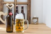 image of glass heart  - I love beer concept with a heart shaped cutout around the neck of a beer bottle alongside a full tankard of beer with a good frothy head on a wooden counter with copyspace - JPG