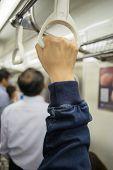 image of passenger train  - Hand of passengers hold on rail handle of transit system train - JPG