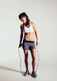 pic of roping  - Studio shot of fit and muscular woman with jumping rope standing on grey background - JPG