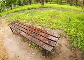 image of distort  - Bench in the park just after a spring rain with wide angle distortion view - JPG