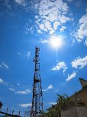 stock photo of distort  - Tower of cellular communication against the blue sky and bright sun with wide angle fisheye lens and distortion view - JPG