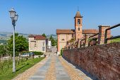 image of cobblestone  - Brick wall along cobblestone walkway and parish church on background under blue sky in Piedmont - JPG