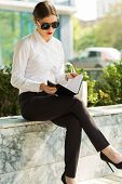 foto of shiting  - Stylish business woman in the city street - JPG