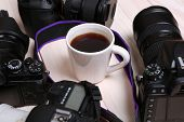 stock photo of megapixel  - Modern cameras with cup of coffee on wooden table - JPG