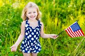 stock photo of usa flag  - Smiling little girl with long curly blond hair holding american flag and waving it outdoor portrait on sunny day in summer park - JPG
