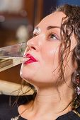 pic of champagne glass  - Beautiful young brunette woman drinking champagne - JPG
