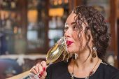 image of champagne glass  - Beautiful young brunette woman drinking champagne - JPG