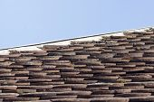 image of roof tile  - Old mossy tiled orange roof on a sunny day - JPG
