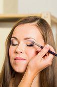 stock photo of makeup artist  - Makeup artist paints the eyebrows model - JPG