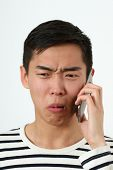 stock photo of disgusting  - Disgusted young Asian man using a smartphone - JPG
