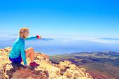stock photo of canary-islands  - Young woman looking at natural beautiful inspirational landscape with islands and ocean hiking trekking and recreation motivation and inspiration in sunny mountains over blue sky and ocean sea Canary Islands - JPG
