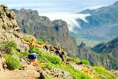stock photo of canary  - Young happy woman running or power walking in mountains on sunny summer day - JPG
