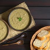 stock photo of dark side  - Cream of lentil soup in rustic bowl with wooden spoons and bread slices in basket on the side photographed overhead on dark wood with natural light - JPG