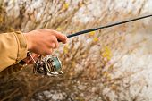 image of fisherman  - Fisherman on the autumn background. Fisherman in his hand holding spinning. Fishing, spinning reel, fish, Breg rivers. - The concept of a rural getaway. Article about fishing. ** Note: Visible grain at 100%, best at smaller sizes - JPG