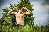 stock photo of grassland  - Handsome fit young man at countryside - JPG