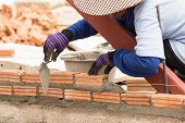 picture of bricklayer  - Bricklayer working in construction site of a brick wall - JPG