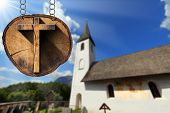 foto of mountain chain  - Wooden Christian cross on a section of tree trunk hanging from a metal chain - JPG