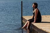 stock photo of jetties  - young lady sitting on the jetty and dips her feet in the cool lake water on a sunny day - JPG