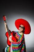 stock photo of sombrero  - Man in red sombrero playing guitar - JPG