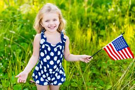 picture of waving hands  - Smiling little girl with long curly blond hair holding american flag and waving it outdoor portrait on sunny day in summer park - JPG