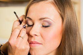 foto of eyebrows  - Makeup artist paints the eyebrows model - JPG