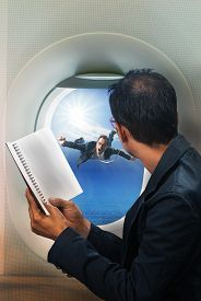 picture of float-plane  - business man reading book in passenger plane seat and looking to out side of plane see another buseness man flying beside a window - JPG