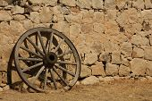 stock photo of stagecoach  - A Butterfield Stagecoach wheel resting against the station wall - JPG