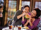 picture of comrades  - Young women fighting to take bite of hamburger - JPG