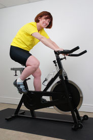 foto of exercise bike  - woman working out on an exercise bike in a home gym  - JPG