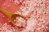 Pink Himalayan salt in spoon. Top view of spoon full of pink Himalayan salt on salt crystal.  poster